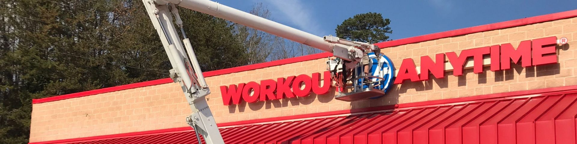 Installing custom building sign for Workout Anytime