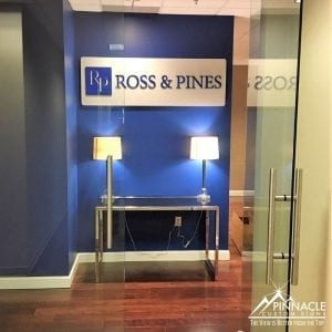 law firm lobby sign uses acrylic on a brushed metal sign